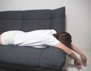 ソファーに腹ばいで寝ている女性の画像.jpg