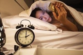 ベッドで横になってスマホを見ている女性の画像.jpg