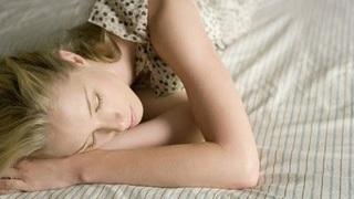 女性が手を枕にしてベッドで寝ている画像.jpg