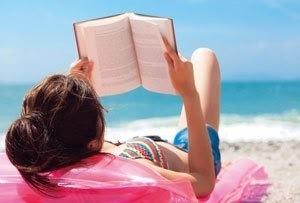砂浜に寝転んで本を読んでいる女性の画像.jpg