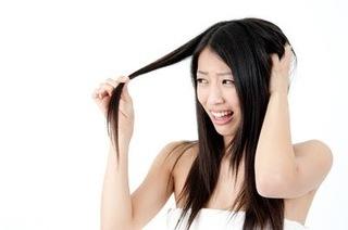 長い髪を手に持つ女性の画像.jpg
