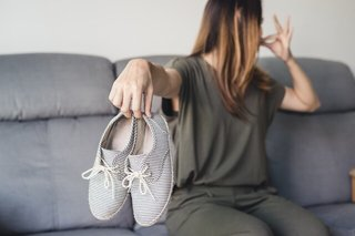 靴を手で持って鼻をつまんでいる女性の画像.jpg